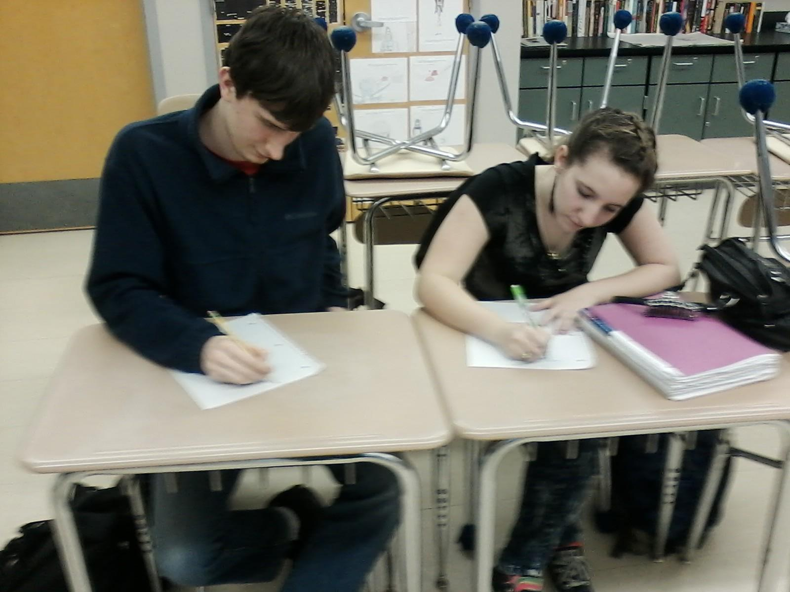 Seniors Taber Hersum and Maesy Edmonstone write their own poems at the Dec. 2 Poetry Club meeting.